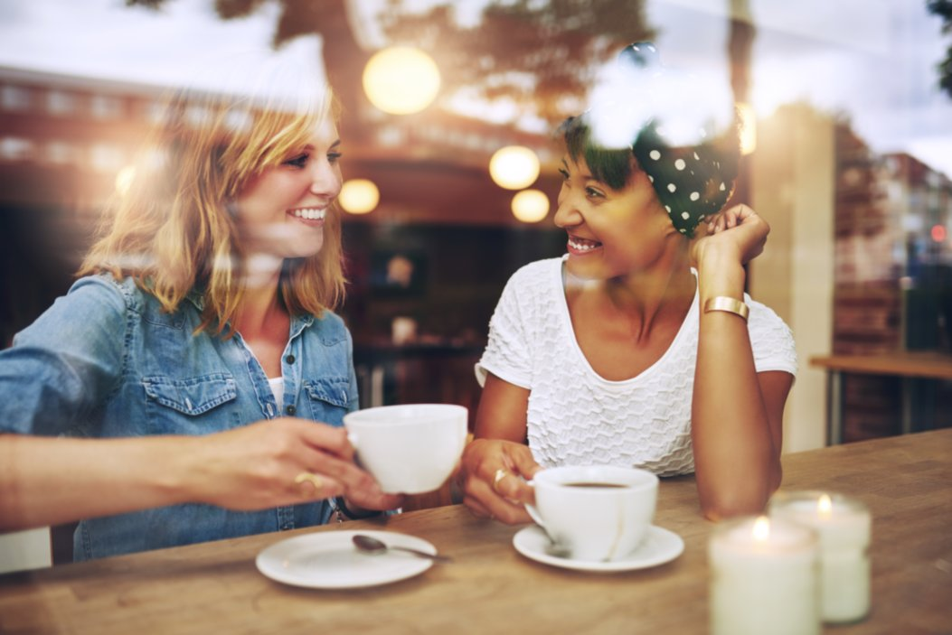 Blonde and brunette woman smiling and drinking coffee